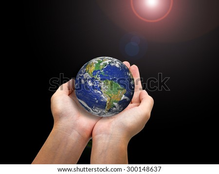 Earth planet in female hand isolated on black and lens flare - Elements of this image furnished by NASA