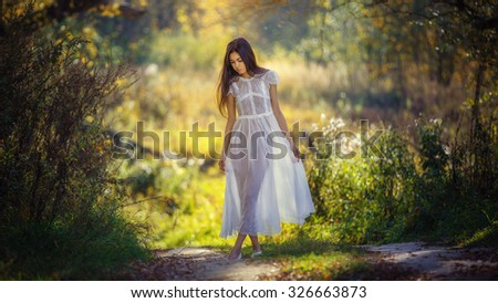 East girl in a white dress on nature in autumn