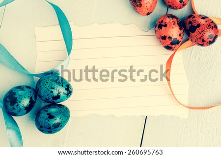 Easter background. Colorful easter eggs on wooden background with easter greeting note paper.