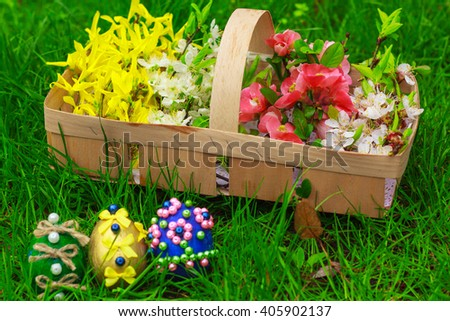 Easter eggs and a basket with flowers on the grass