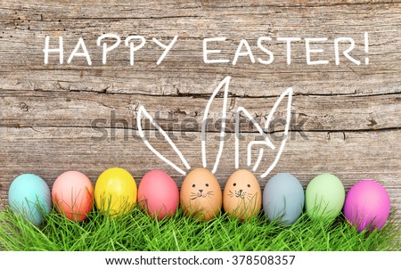Easter eggs and cute bunny in green grass. Festive decoration. Happy Easter!
