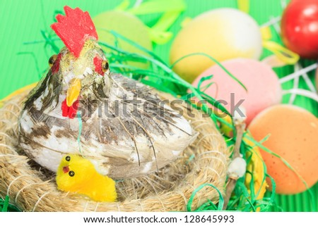 Easter eggs and nest with a hen and chickens on festive background .