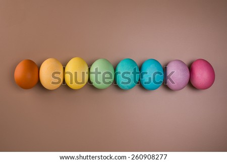 Easter eggs in row on beige background