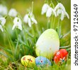 easter eggs  on meadow with snowdrops and sun - stock photo