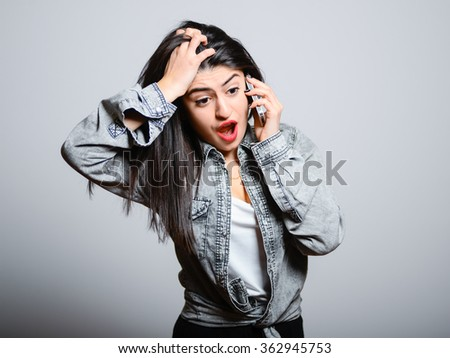 Eastern irritated brunette talking on a cell, hipster denim clothing, photo studio, portrait emotions