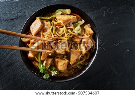 eating japanese chicken yakisoba with chopsticks in flat lay composition