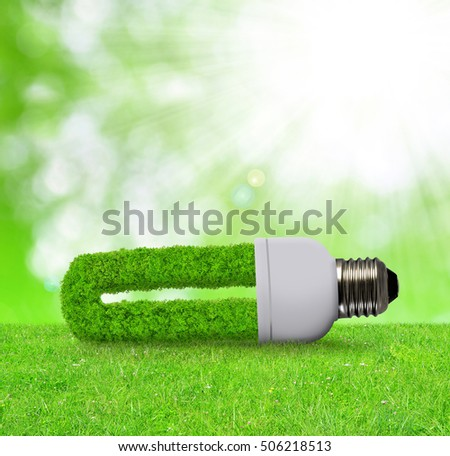 Eco light bulb in grass  - Green energy concept.