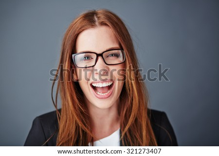 Ecstatic young businesswoman in eyeglasses looking at camera