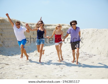 Ecstatic young people holding by hands while running down beach