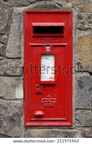 EDINBURGH, SCOTLAND --21 JUNE 2014-- A red mailbox for the Royal Mail, the British postal service, is mounted in a stone wall in a street in Edinburgh, Scotland.