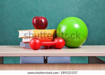 Education concept. Colorful school accessories (apple, books, ball) on table