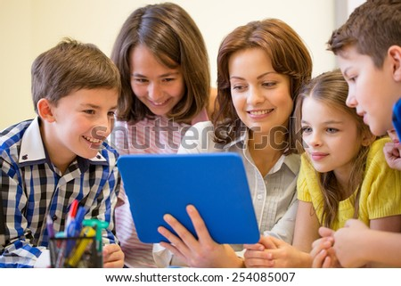 education, elementary school, learning, technology and people concept - group of school kids with teacher looking to tablet pc computer in classroom