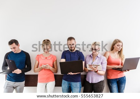 Education social media concept. Male and female diversity students young people studying using computer tablet smartphone, standing on wall with copy space