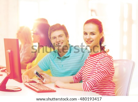 education, technology and school concept - smiling student with smartphone in computer class