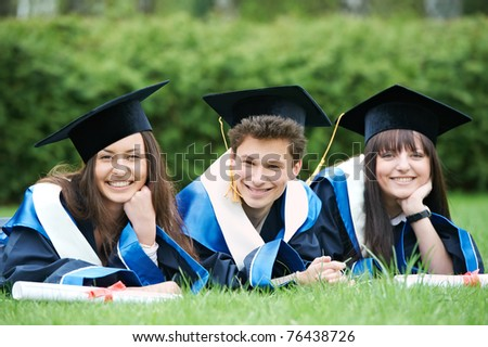education theme of graduate students lying in the park cheerful and happy