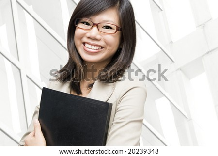 Educational / business people. Young Asian women holding a file in office environment.