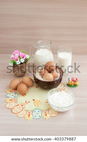 Eggs and milk on a napkin embroidered. Chicken eggs in the straw in the cup. Milk in a jug and a glass for a healthy breakfast. Products on an embroidered napkin. Eggs can be used for Easter.