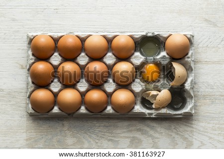 Eggs in an egg container, one of the eggs broken.