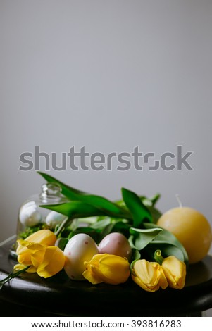 Eggs with tulips and candle on the table