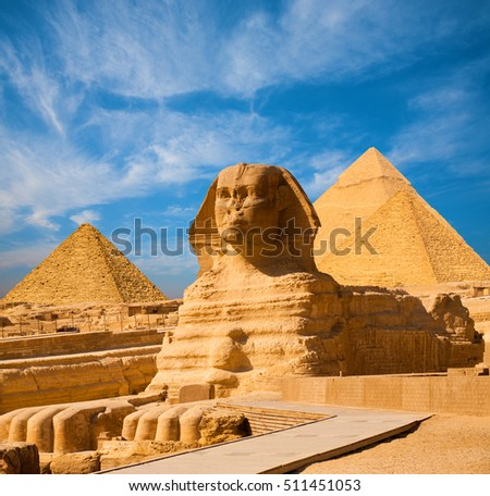 Egyptian Great Sphinx full body portrait with head, feet with all pyramids of Menkaure, Khafre, Khufu  in background on a clear, blue sky day in Giza, Egypt empty with nobody. copy space