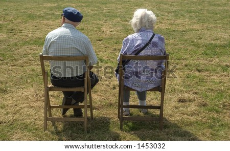 Elderly couple sitting quietly in field