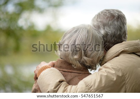 Elderly couple  with his back embracing in autumn park