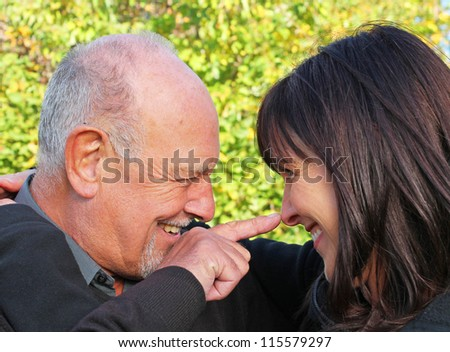 Elderly father and daughter laughing and joking