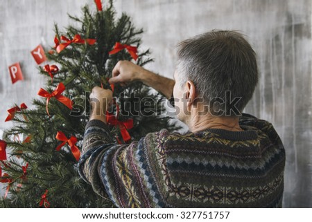Elderly man decorating the fir-tree with red bows. Back view