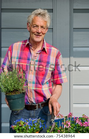 Elderly man is working with plants in the garden