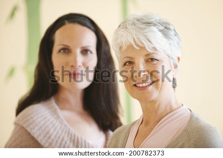 Elderly mother and adult daughter together smiling close up