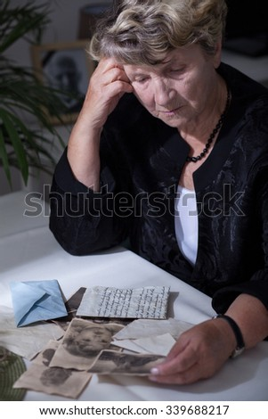 Elderly woman in mourning watching old photos