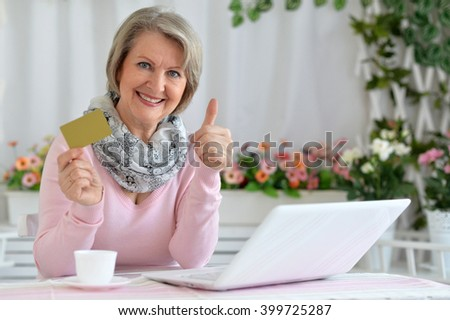 elderly woman making purchases on the internet while sitting at the table