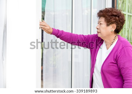 Elderly woman opening home entrance door