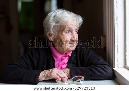 Elderly woman, portrait near the window.