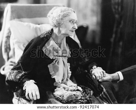Elderly woman sitting in a chair holding a man's hand