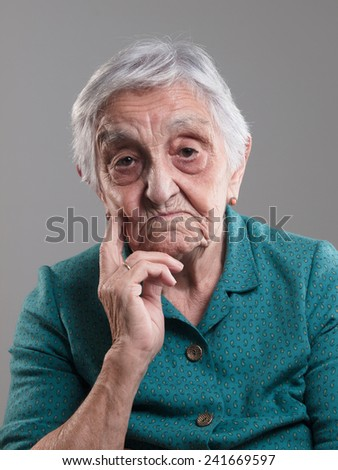 Elderly woman smiling with a flower in her ear in a studio shot.