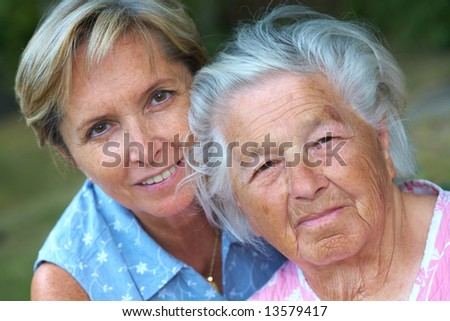 Elderly woman with her daughter. Focus on the senior woman.