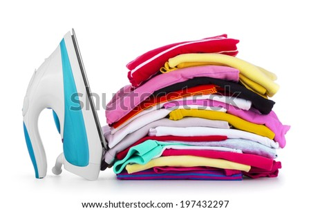 Electric iron and pile of colorful clothes, isolated on white