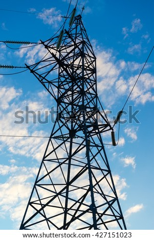 Electric power transmission against sky at sunset