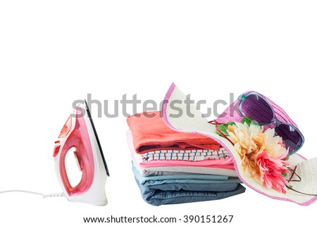 electric steam iron and Pile of colorful clothes isolated on white background