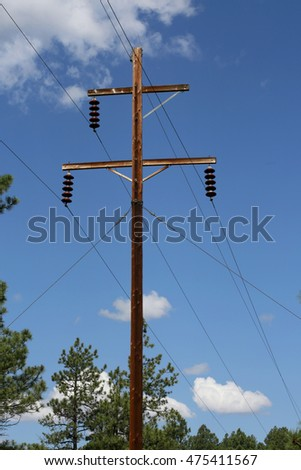 Electrical pylon against the cloudy blue sky and pine trees. Close up.