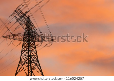 electricity pylon silhouetted against the sunset