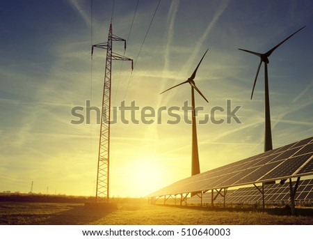 Electricity transmission pylon with solar panels and wind turbines on field against the sunset.