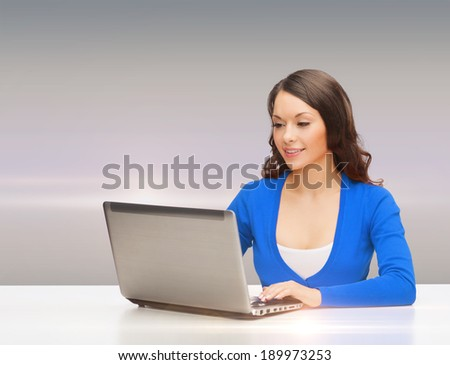 electronics and gadget concept - smiling woman in blue clothes with laptop computer
