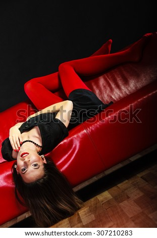Elegance and fashion outfit. Fashionable woman legs in red vivid color tights posing on couch black background