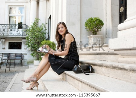 Elegant businesswoman sitting on a classic buildings steps taking notes in her agenda, smiling.