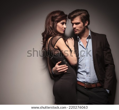 Elegant couple embracing and looking at each other. The man is holding one hand in his pocketOn dark grey background.