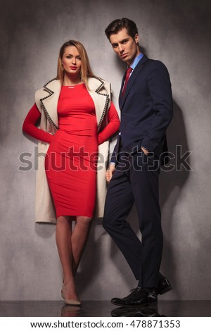 elegant couple standing in studio, man in suit and tie with hand in pocket, woman in red dress and long wool coat standing with hands at her back