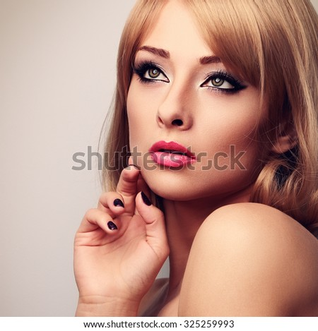 Elegant green eyes woman looking up with perfect makeup and blond hairstyle. Closeup toned portrait