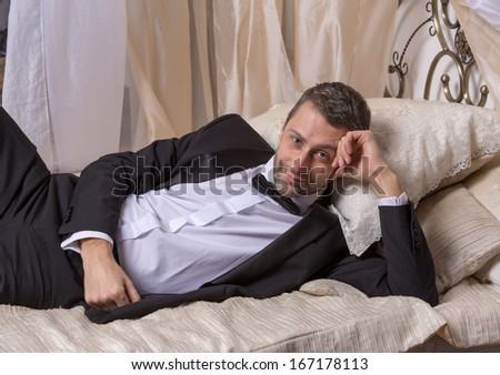Elegant handsome playboy in a bow tie and suit reclining on a bed in an elaborate bedroom with a seductive smile on his face